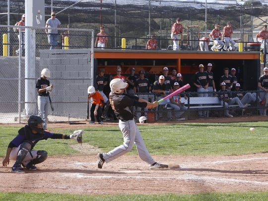 Aztec's Cody Smith hits a two-RBI double against Kirtland Central on Thursday in Aztec.