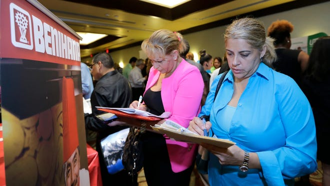 Job seekers Madelin Garcia, right, and Noharis Nunez fill out  job applications at a job fair in Miami Lakes, Fla. in October.