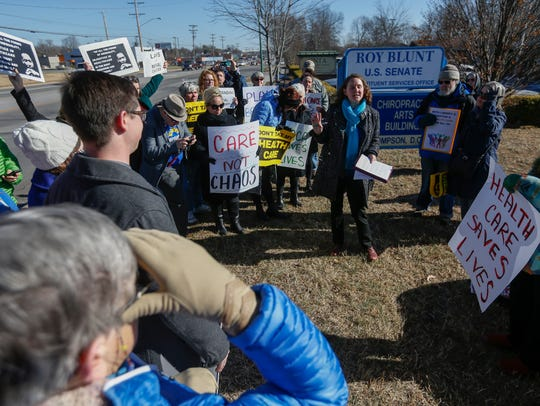 People in favor of the Affordable Care Act stand outside