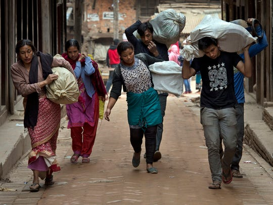 Residents carry their belongings that were retrieved from ruins of their homes after Saturday's earthquake in Bhaktapur, Nepal on Tuesday. Many people have camped outdoors in the chilly night cold since Saturday's massive earthquake that shook Nepal's capital and the densely populated Kathmandu valley.