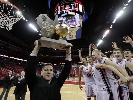 Stevens Point Area Senior High head coach Scott Anderson lifts the trophy after his team defeated Arrowhead High School in the Division I championship game at the 2017 boys basketball state tournament on March 19 at the Kohl Center in Madison.