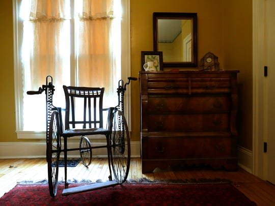 A late 1800s-style wheelchair stands in a bedroom as part of a Civil War exhibit at the Neenah Historical Society.