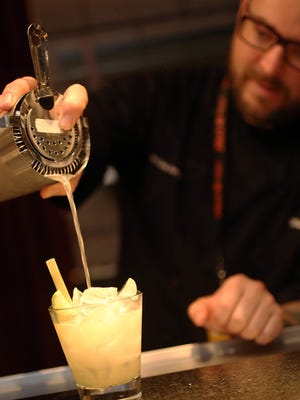 A mixologist pours a drink during the Arizona Storytellers event, part of Arizona Cocktail Week.