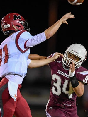 Isaiah Fallen (34) puts pressure on McCracken County quarterback Elijah Wheat (11) in Henderson's 40-25 loss on Friday night at Colonel Field.