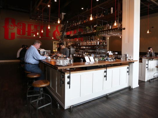 Customers sit at the bar at Archive Coffee & Bar in