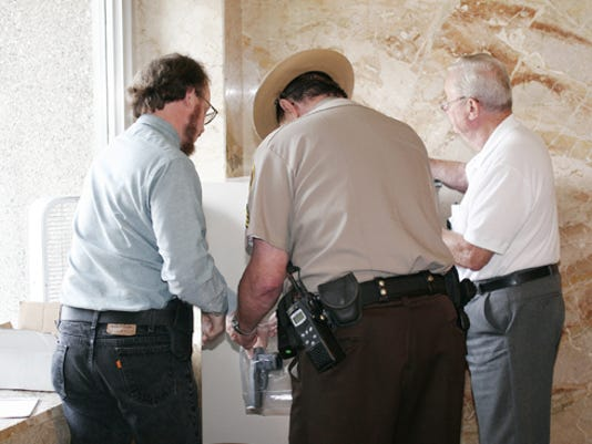 David Rothschild (left) of Ambler turns over his gun to Sgt. Ferdy Sammer of the county sheriff s department and security worker Marlin Long so he may enter the courthouse yesterday.