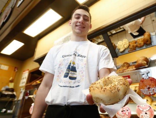 Everett Sobel holds an everything bagel at Goldbergs's