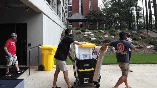 College students move in for the fall semester at North Carolina State University in Raleigh. The school announced it would close residence halls less than a week after moving classes online because of COVID-19.