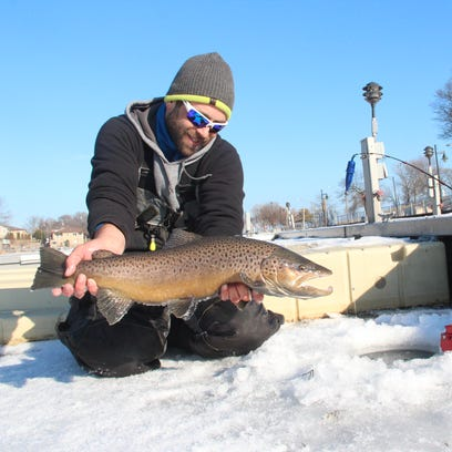 Joe Boutell of Racine prepares to release a brown trout
