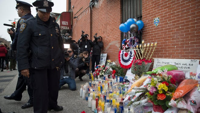 Mourners visit a makeshift memorial, on Dec. 22, 2014, near the site where New York Police Department officers Rafael Ramos and Wenjian Liu were murdered in Brooklyn.