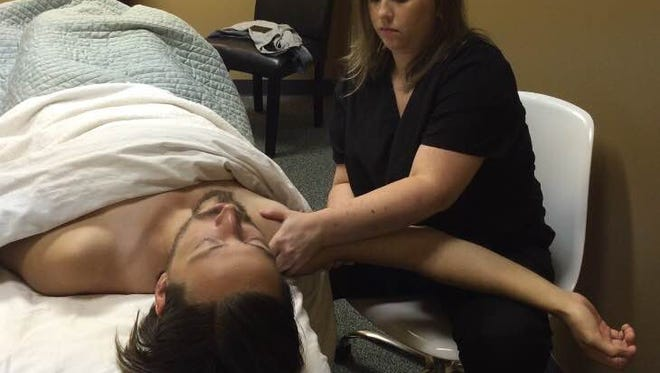Sarah Trueb, CMT, demonstrates shoulder work on Kody Hall at the Orthopedic Massage Rehabilitation Center in Lafayette.
