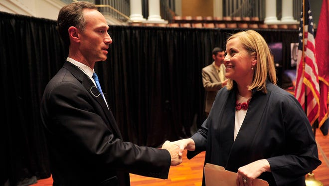 Megan Barry shakes hands with David Fox after a runoff debate at Belmont University.