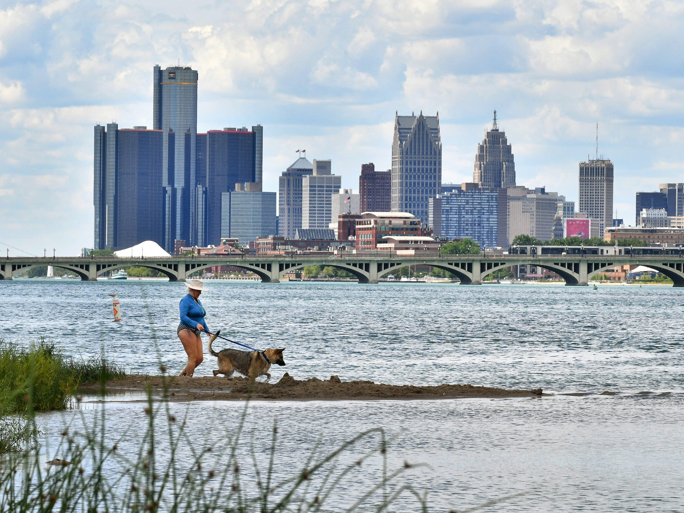 "Laura Che and Stella enjoy the cool water with the Detroit skyline from Belle Isle in Detroit on Tuesday. Michigan born Laura Che is back visiting from California: ""I had to come back and have a Michigan summer. Oh my gosh, I love this area, they let me bring my dog on a leash. Since the bankruptcy, there has been improvement; it was in a very sad decline."""
