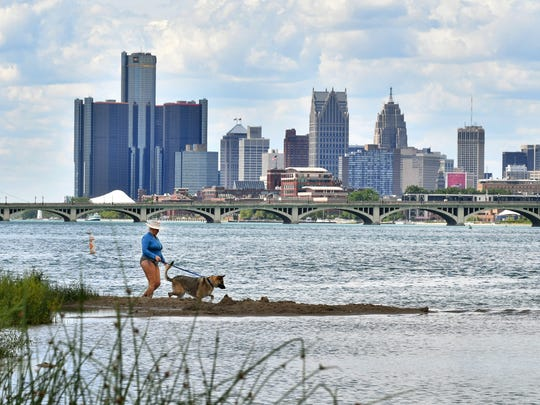 """Laura Che and Stella enjoy the cool water with the Detroit skyline from Belle Isle in Detroit on Tuesday. Michigan born Laura Che is back visiting from California: """"I had to come back and have a Michigan summer. Oh my gosh, I love this area, they let me bring my dog on a leash. Since the bankruptcy, there has been improvement; it was in a very sad decline."""""""