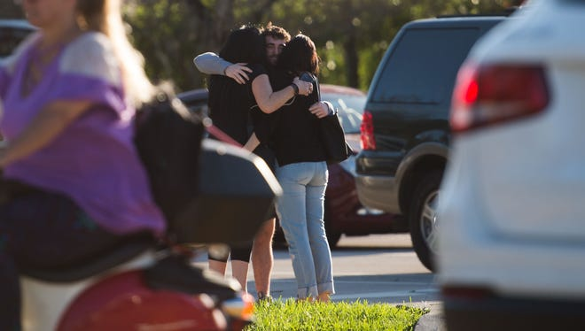 Students, family members and staff from nearby Marjory Stoneman Douglas High School reunite Wednesday, Feb. 14, 2018, at University Drive and Holmberg Road after a mass shooting in Parkland.