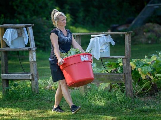 Bobbie Jo Axelrod, 45, carries a bushel of collards