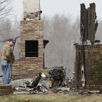 A man looks over a home that was destroyed by fire
