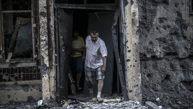 People come out from their houses after shelling in Donetsk, Ukraine, on July 29, 2014.