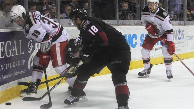 Grand Rapids Griffins forward Tyler Bertuzzi, left, battles for a puck against Lake Erie.