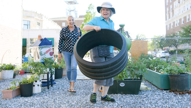 Clare Hanrahan, coordinator of Elder & Sage community gardens carries a planter donated by West Asheville resident Carol More, left, at the downtown garden on Tuesday, June 27, 2017.