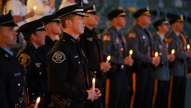 Camden County Chief of Police Scott Thomson, center, along with officers from other agencies participate in a candlelight vigil at Camden's waterfront stadium.