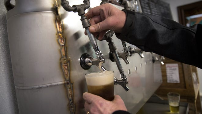 Mike Paschall, owner of 550 Brewing, pours himself a beer, Wednesday, Jan. 18, 2017 at The Hub on 119 East Chuska Street in Aztec.