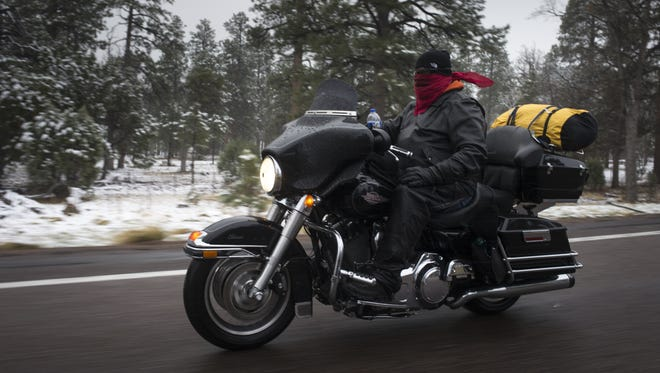 A motorcyclist rides in the sleet Wednesday May 2, 2018, on Highway 260 east of Forest Lakes, Arizona.
