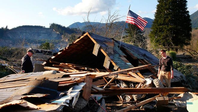 Brian Anderson, left, and Coby Young search through the wreckage of a home belonging to the Kuntz family Sunday, March 23, 2014, near Oso, Wash. The entire Kuntz family was at a baseball game Saturday morning when a fatal mudslide swept through the area. The family returned Sunday to search through what remained.