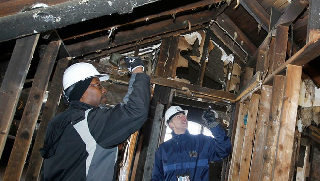David Dorsey (left) of the Milwaukee Department of City Development and Jeff Sporer of the Department of Neighborhood Services check the attic of a fire-damaged foreclosed home in the 3000 block of N. Sherman Blvd. Wednesday. The city inspectors look at 15 to 20 homes per week to assess any needed repairs before making the houses available to the public.