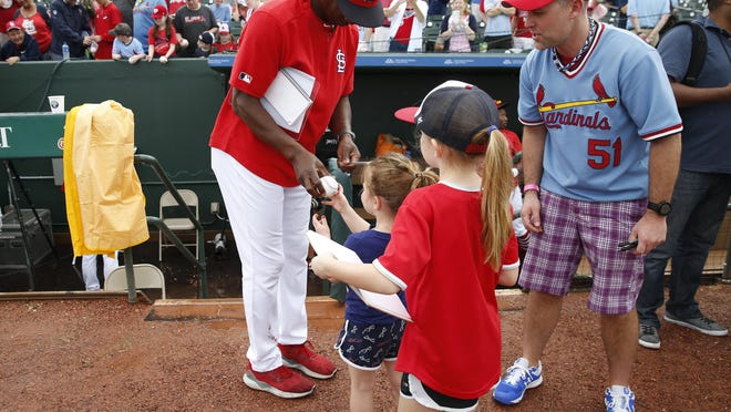 St. Louis Cardinals assistant coach Willie McGee (51) signs a fan's shirt before an exhibition spring training game against the Houston Astros on Saturday, March 9, 2019, in Jupiter, Fla.