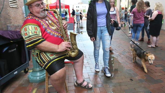 """Denny Ott plays the saxophone outside Joe Albert Studios on Court Avenue NW during First Friday's activities in downtown Canton on Friday, June 1, 2018. This month's theme is """"Gone to the Dogs,"""" a salute to dogs and those who love them."""