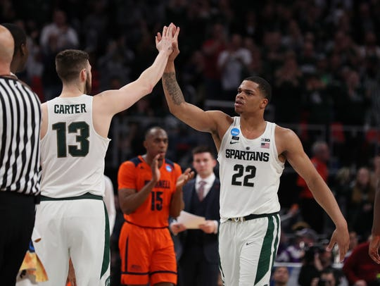 Michigan State's Ben Carter high-fives teammate Miles
