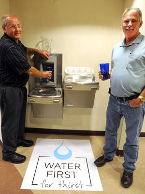 Marion County Commissioners Ken Stiverson and Dan Russell try out the new tall-container water dispenser installed at a drinking fountain in the Marion County Building.