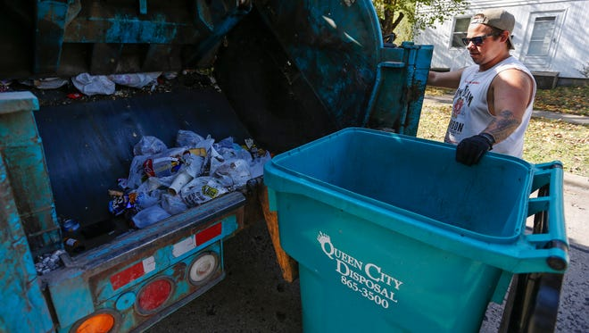Thomas Nault, of Queen City Disposal, picks up trash on Prospect Avenue on Wednesday, Nov. 2, 2016.
