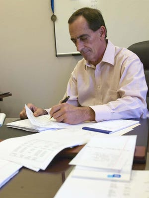Jim Amodeo, Sheboygan Chief Administrative Officer, does some paper work in his office at City Hall.