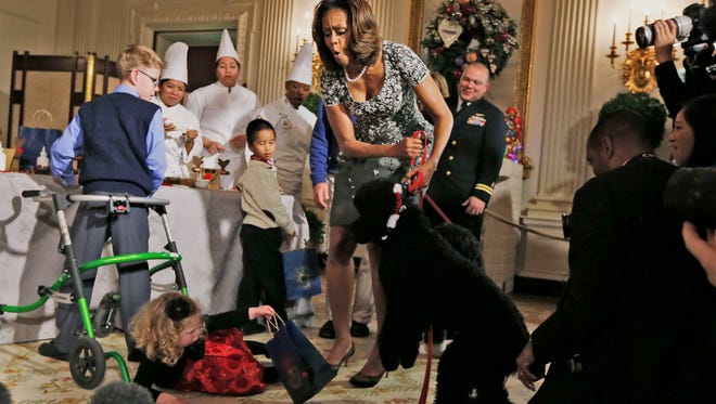 First lady Michelle Obama reacts as Ashtyn Gardner, 2, from Mobile, Ala., loses her balance when she was greeting Sunny, one of the presidential dogs.