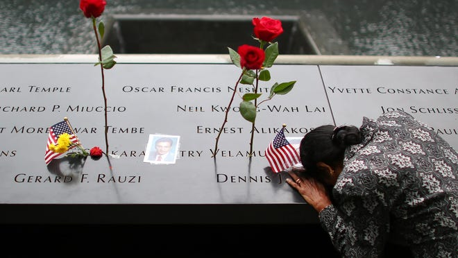 A woman grieves at her husband's memorial at the South Tower Memorial Pool during memorial observances on the 13th anniversary of the Sept. 11, 2001 terror attacks on the World Trade Center in New York, Thursday, Sept. 11, 2014. Family and friends of those who died read the names of the nearly 3,000 people killed in New York, at the Pentagon and near Shanksville, Penn.