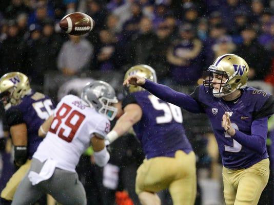 Washington quarterback Jake Browning, right, throws a pass against Washington State during the first half of an NCAA college football game, Saturday, Nov. 25, 2017, in Seattle. (AP Photo/Ted S. Warren)