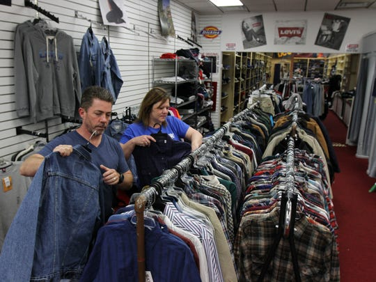 Harry and Diane Arnold, owners of Jam Apparel, located in Airport Plaza on Route 36 in Hazlet arrange inventory in the store.