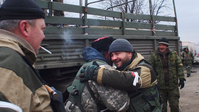 A pro-Russian rebel cossack, second left, hugs another rebel in Debaltseve, eastern Ukraine, Thursday, Feb. 19, 2015. After weeks of relentless fighting, the embattled Ukrainian rail hub of Debaltseve fell Wednesday to Russia-backed separatists, who hoisted a flag in triumph over the town.