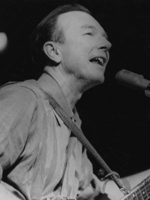 Pete Seeger performs at a 1965 peace rally in New York City.
