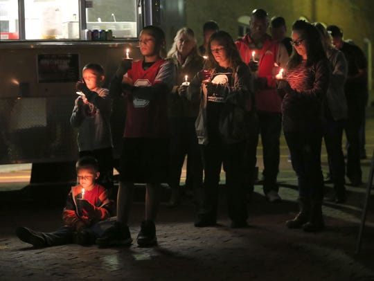 Attendees of a candle lighting held in memory of those