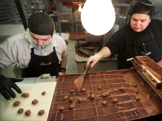 Andrew Dinstuhl, left, demonstrates the decorative squiggle on the top of chocolates while making chocolate-covered grapes with Rose Rubio.