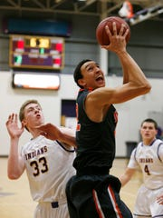 Ames' Javan White takes a shot ahead of Indianola's Taylor Constable (33) on Jan. 20.
