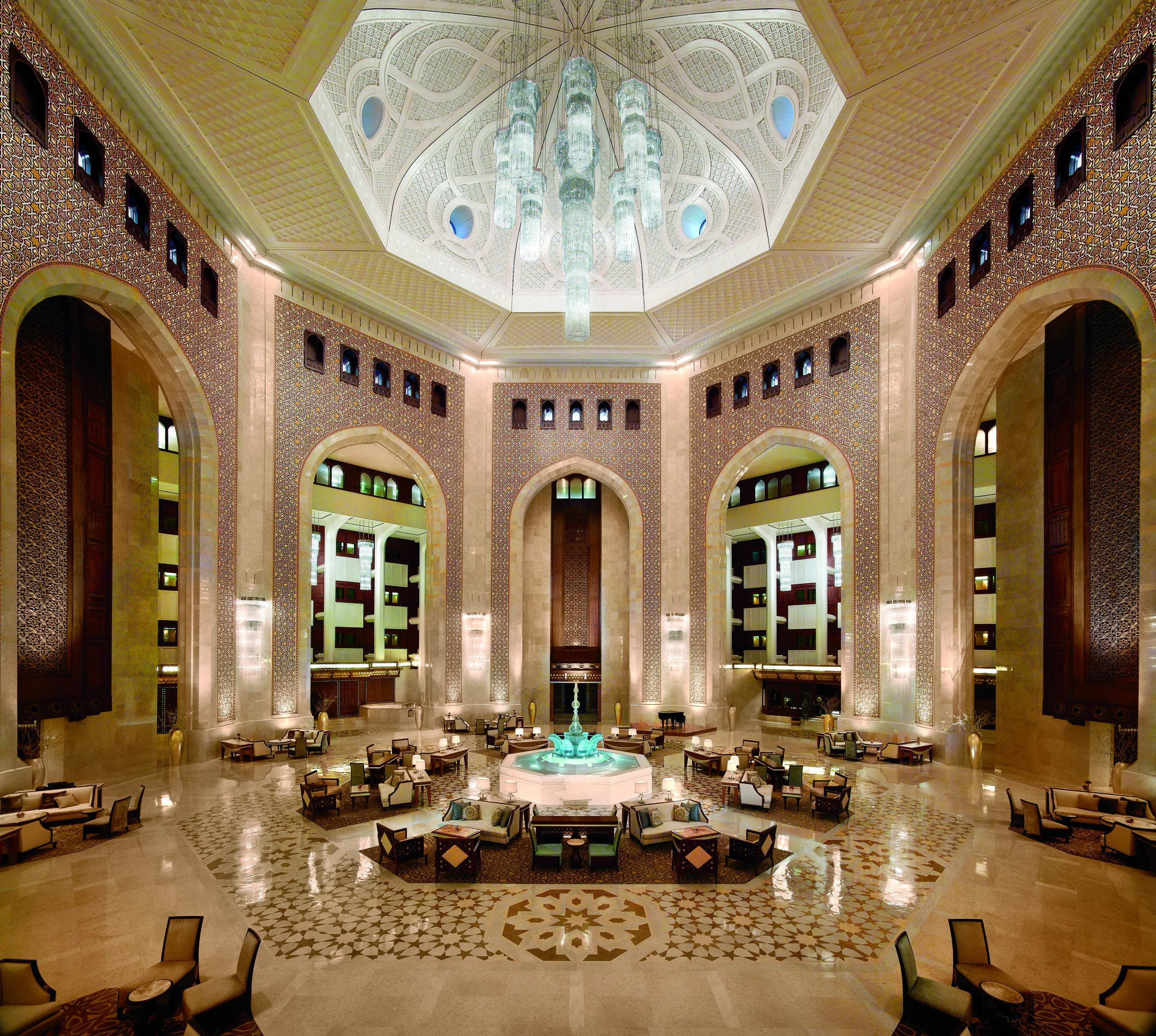 The Atrium Lobby of Al Bustan Palace, a Ritz-Carlton property in Oman, features a majestic ceiling and is encircled by bold arches.