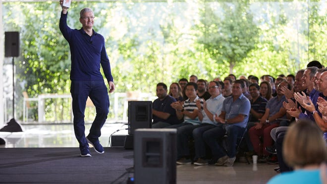 Apple CEO, Tim Cook holds up the billionth iPhone at an employee meeting in Cupertino. CA  Wednesday morning.