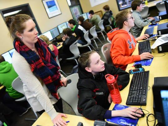 Computer Science Teacher Andrea Reece helps freshman