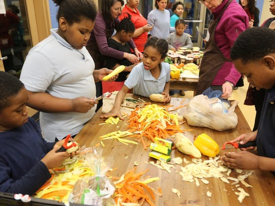 Children and parents take part in family cooking class at Born Learning Academy in John P. Parker School in Madisonville. The class, taught by La Soupe aims to  teach basic knife and kitchen skills.