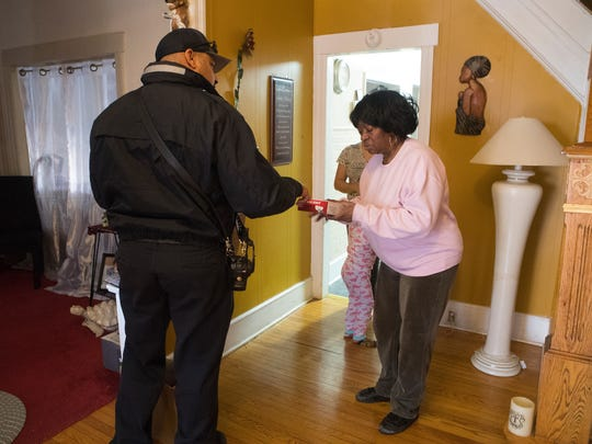 Wilmington Senior Firefighter BJ Silva hands a smoke detector to Sarah Temple during a canvassing operation to make sure residents have working smoke detectors in their homes in the north side of Wilmington on Monday.