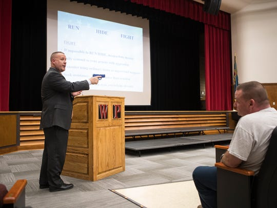 Detective Timothy Kerstetter with the Delaware State Police  uses a fake handgun to demonstrate preemptive measures that can be taken to stop an active shooter during a Violent Intruder Preparedness & Response training seminar Monday at William Penn High School.